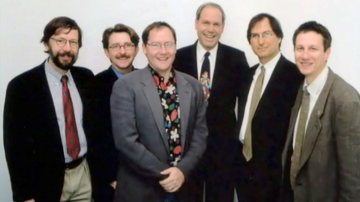 Steve Jobs poses with Disney CEO Michael Eisner (middle, dark suit) and Pixar's Ed Catmull (left-most) and John Lasseter (middle, grey suit), 1995