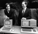 Steve Jobs poses with Macintosh while Sculley rests on a LISA