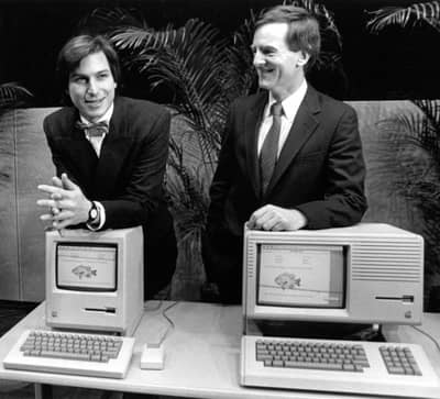 6 Feb 1984 - Steve Jobs poses with Macintosh while Sculley rests on a LISA