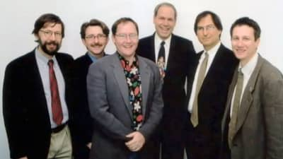 1995 - Steve Jobs poses with Disney CEO Michael Eisner (middle, dark suit) and Pixar's Ed Catmull (left-most) and John Lasseter (middle, grey suit)